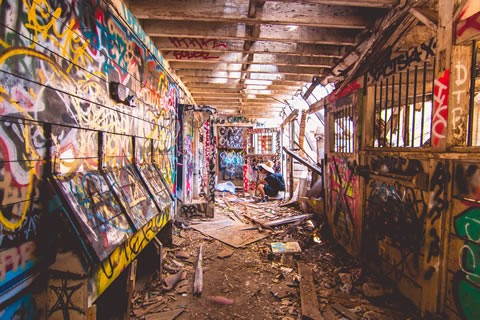 Young man taking a photo while crouching down in an abandoned house with graffiti on every surface
