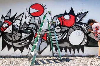 """Photo of Fathima Mohiuddin working on her mural """"Flight"""""""