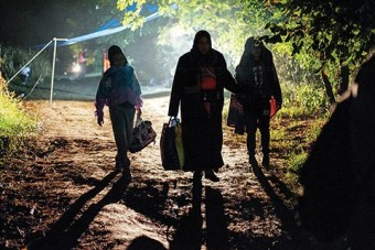 Photo of three refugees walking on a dirt path with their belongings at night
