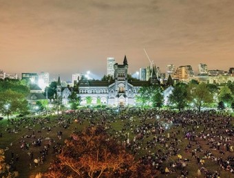 Evening photo of a large crowd of spectators at King's College Circle