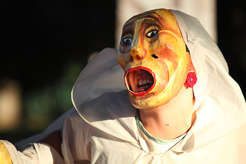 Photo of a puppeteer performing in a clay mask and white hood