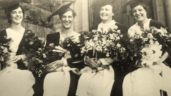 Old photo of Elizabeth Cranston and three other women sitting down in robes holding flowers