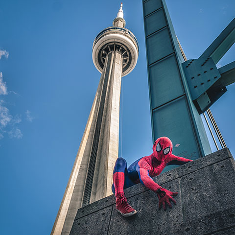 Photo of CN Tower against blue sky in the background and performer in a Spiderman suit crouching at the forefront