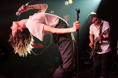 Photo of July Talk in concert with Leah Fay bending backward