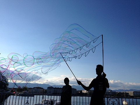 Photo of two figures in shadow, one holding up a large bubble maker with bubbles blowing through, by Lake Geneva