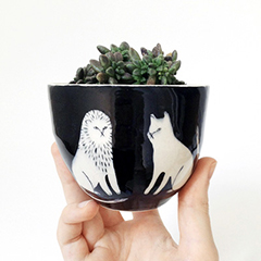 Photo of a cup with black and white designs of a lion and a cat