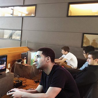 Photo of Drake sitting at a student lounge, playing video games