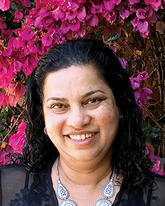 Headshot photo of Jeewika Ranaweera with pink flowers in the background