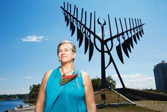 Outdoor photo of Margaret Froh standing in front of Barrie's Spirit Catcher sculpture