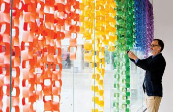 Photo of Trevor Young adding paper loops to the Faculty of Medicine's Display Your Pride installation