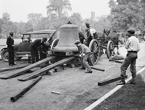 Photo of workers unloading a large bell from a horse-drawn wagon