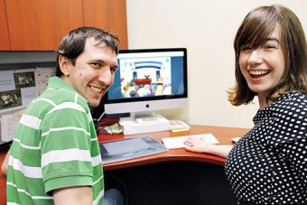 Photo of Chris Primerano and Heather Shanahan sitting in front of a computer screen displaying the game