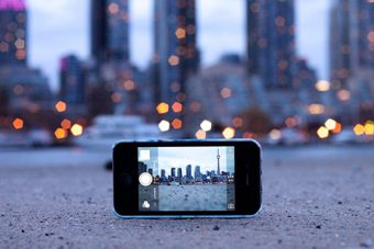 Photo of an iPhone camera with the Toronto skyline in focus on the screen and out of focus behind