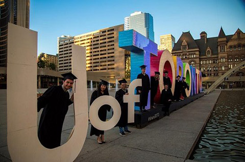 """Photo of engineering students in convocation gowns holding the letters """"U of"""" on the left of the """"Toronto"""" sign at City Hall"""