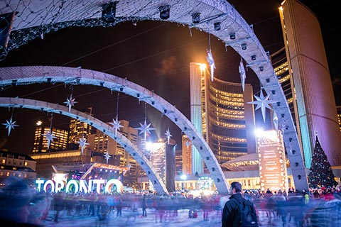 Photo of ice rink and Toronto sign at Nathan Phillips Square during Cavalcade of Lights, with skaters blurred and a man appearing clearly at the bottom right