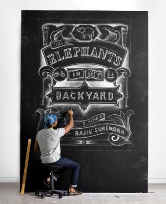 """Photo of Rajiv Surendra drawing the cover of """"The Elephants in My Backyard"""" on a large chalkboard"""