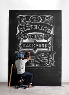 "Photo of Rajiv Surendra drawing the cover of ""The Elephants in My Backyard"" on a large chalkboard"