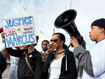 """Photo of a group of protesters, one speaking through a loudspeaker and one holding a sign (""""Justice 4 Marcus. Disregard for black lives = Legal white supremacy)"""