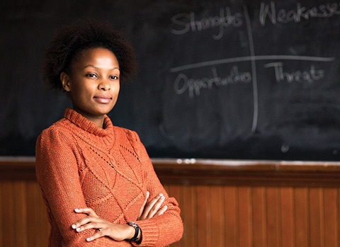 Photo of Sylvia Mwangi in front of a classroom chalkboard