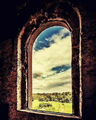 Photo of a window in an abandoned house overlooking a green field and forest