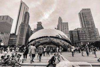 Black and white photo of a crowd in front of Chicago's Cloud Gate sculpture (the Bean), including families and a wedding couple kissing on the steps