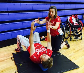 Photo of Agnes Makowski working with an athlete, who is lying on a mat