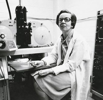 Photo of Ursula Franklin in a lab surrounded by equipment