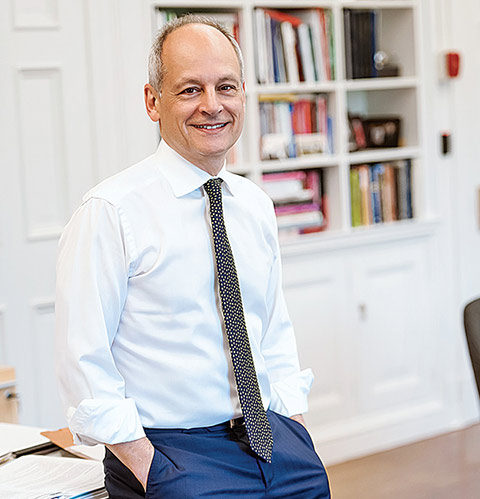 Meric Gertler leaning on a desk in his office