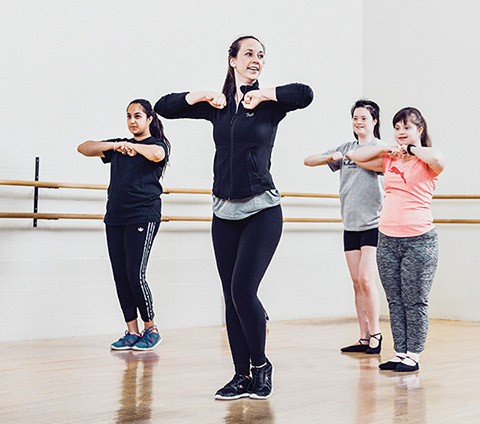 Photo of Neha Singh and Jade Ryan teaching a dance move to two young dancers.