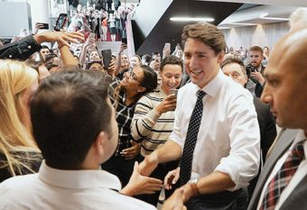 Photo of Justin Trudeau greeted by a large crowd of students inside Rotman.