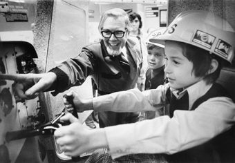 Bernard Etkin pointing at a feature, speaking to two boys wearing hard hats, one of whom is steering the simulator.
