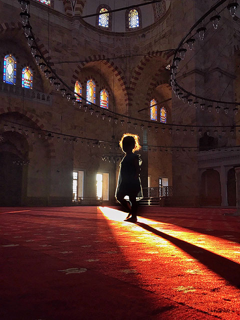 Photo of a little girl in silhouette standing in a beam of sunlight from a window inside a mosque