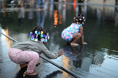 Photo of two young children playing, crouched down on wet pavement.
