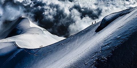 Photo of two pairs of hikers walking along the summit of Aiguille du Midi.