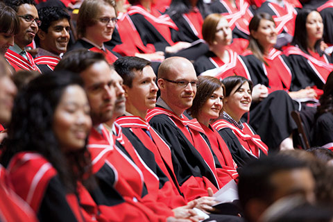 Close up photo of PhD graduates in robes sitting attentively during convocation ceremony.
