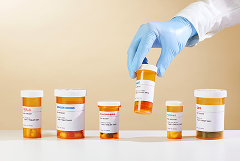 Photo of a plastic-gloved hand picking up the fourth of six prescription medicine containers in a row.
