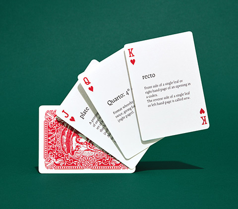 "Photo of four cards, the top three facing up showing the Jack, Queen and King of hearts with definitions for ""plate,"" ""quarto,"" and ""recto"" in the centre of the respective cards."