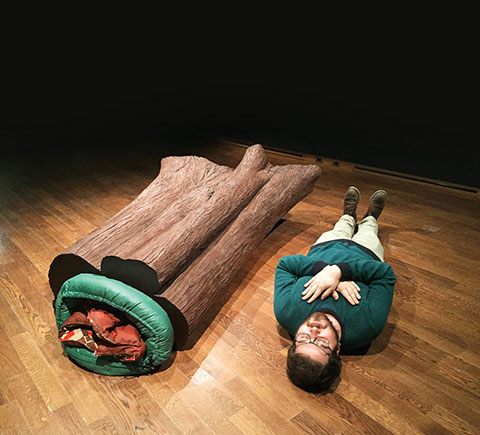 Photo of an art installation of a sleeping bag inside a log on the left and a man lying with eyes closed on the right.