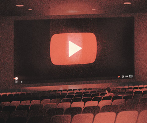 "Illustration of seats in a movie theatre with the screen showing the ""play"" arrow click button at the start of YouTube videos."
