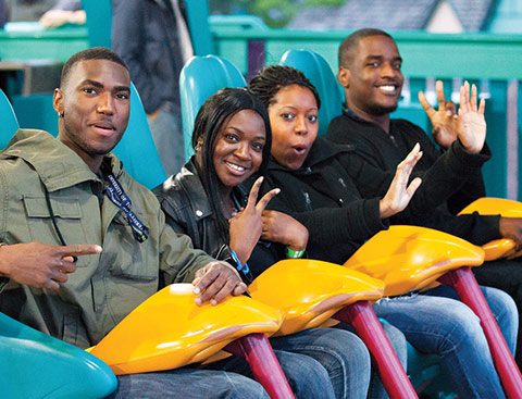 Four alumni posing for a photo while sitting in one row of a rollercoaster ride.