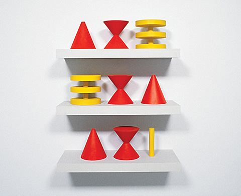 Photo of red and yellow objects of various repeating shapes sitting on three, white shelves mounted on a white wall.