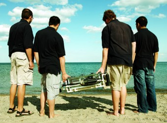 Photo of men on the beach with the aquabot