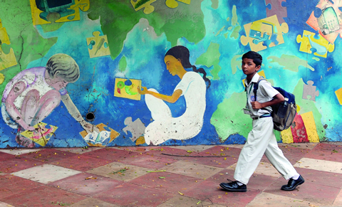 A child walking past a mural in Mumbai