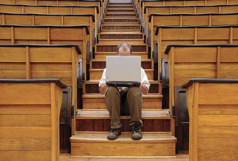 Photo of a person sitting on wood stairs behind a laptop.