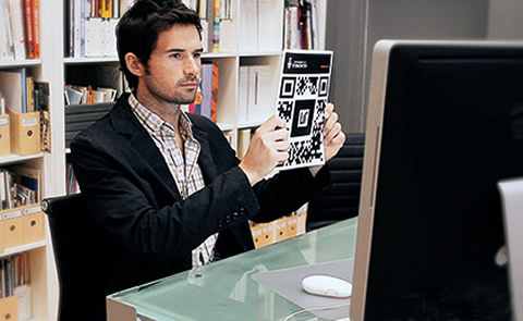 Photo of a man holding a sheet of QR codes