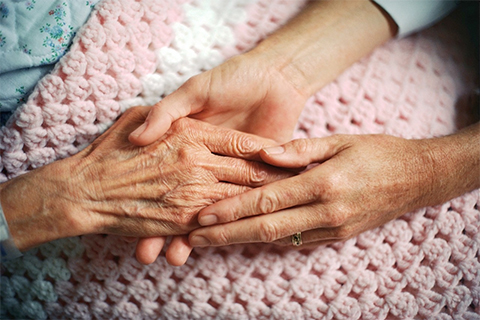 Photo of a woman's hands holding an elderly woman's hand.