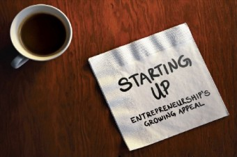 "A serviette on a table that has written on it: ""Starting Up: entrepreneurship's growing appeal"""