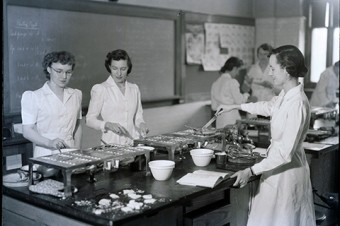 Photo of women at cooking stations in the faculty of household science.