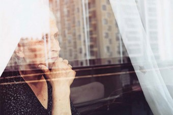 Photo of an elderly woman looking pensively out a window.