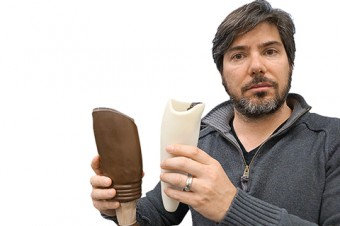 Prof. Matt Ratto holds a conventional prosthetic socket (left) and one his lab printed.